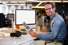 Συνεδρίαση συντακτών φωτογραφιών χαμόγελου στο γραφείο υπολογιστών Στοκ φωτογραφία με δικαίωμα ελεύθερης χρήσης