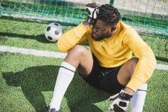Συνεδρίαση τερματοφυλακάων αφροαμερικάνων στο goalpost στην πίσσα Στοκ Εικόνες