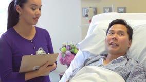 Συνεδρίαση της ιατρικής ομάδας γύρω από τον αρσενικό ασθενή στο δωμάτιο νοσοκομείων απόθεμα βίντεο