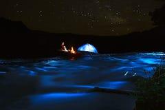 Συνεδρίαση τουριστών κοντά στη σκηνή από την πυρά προσκόπων στις όχθεις του ποταμού τη νύχτα Στοκ Φωτογραφίες