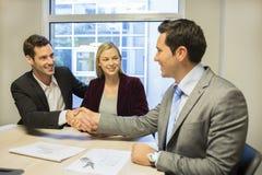 Συνεδρίαση του ζεύγους με τον οικονομικό σύμβουλο, χειραψία στοκ φωτογραφία