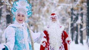 Συνεδρίαση του παγετού κοριτσιών χιονιού Snegurochka και πατέρων Ded Moroz στα χειμερινά δασικά και κυματίζοντας χέρια απόθεμα βίντεο