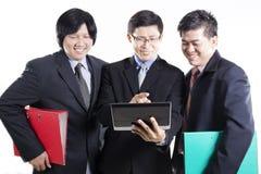 Συνεδρίαση των τριών επιχειρηματιών και χρησιμοποίηση της ταμπλέτας Στοκ εικόνα με δικαίωμα ελεύθερης χρήσης