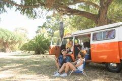 Συνεδρίαση φίλων με το φορτηγό τροχόσπιτων στη θέση για κατασκήνωση στοκ φωτογραφία με δικαίωμα ελεύθερης χρήσης