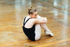 Συνεδρίαση Ballerina στο ξύλινο πάτωμα Στοκ Εικόνες
