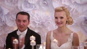 Συνεδρίαση Newlyweds σε έναν πίνακα στο γάμο της που επιδοκιμάζει και που χαμογελά κοντά επάνω απόθεμα βίντεο