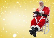 Συνεδρίαση Santa στην καρέκλα και χρησιμοποίηση της ψηφιακής ταμπλέτας Στοκ Φωτογραφία