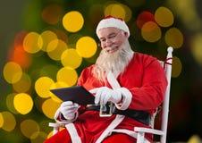 Συνεδρίαση Santa στην καρέκλα και χρησιμοποίηση της ψηφιακής ταμπλέτας Στοκ Εικόνες