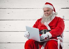 Συνεδρίαση Santa στην καρέκλα και χρησιμοποίηση του lap-top Στοκ φωτογραφία με δικαίωμα ελεύθερης χρήσης
