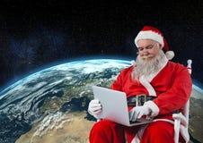 Συνεδρίαση Santa στην καρέκλα και χρησιμοποίηση του lap-top Στοκ Εικόνα