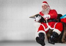 Συνεδρίαση Santa στον καναπέ και το βιβλίο ανάγνωσης Στοκ Εικόνες