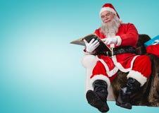 Συνεδρίαση Santa στον καναπέ και το βιβλίο ανάγνωσης Στοκ φωτογραφία με δικαίωμα ελεύθερης χρήσης