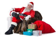Συνεδρίαση Santa στον καναπέ με το σάκο του χριστουγεννιάτικου δώρου εκτός από τον Στοκ Εικόνες