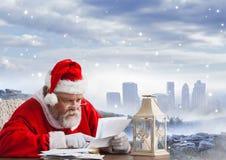 Συνεδρίαση Santa στον πίνακα και την επιστολή Χριστουγέννων ανάγνωσης Στοκ εικόνα με δικαίωμα ελεύθερης χρήσης