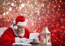 Συνεδρίαση Santa στον πίνακα και την επιστολή Χριστουγέννων ανάγνωσης Στοκ Εικόνες