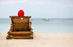 Συνεδρίαση Santa στο μόνιππο longue στην παραλία Στοκ Φωτογραφίες