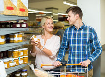 Συνηθισμένη οικογένεια που αγοράζει τα κονσερβοποιημένα τρόφιμα για την εβδομάδα α Στοκ Εικόνα