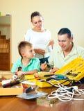 Συνηθισμένη συμπαθητική οικογένεια τριών που κάνουν κάτι με την εργασία Στοκ Εικόνες