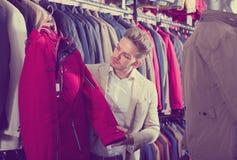 Συνηθισμένος αρσενικός πελάτης που εξετάζει τα παλτά Στοκ εικόνες με δικαίωμα ελεύθερης χρήσης