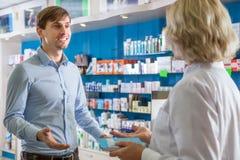 Συνηθισμένος τύπος που μιλά στο φαρμακοποιό στο φαρμακείο στοκ εικόνα