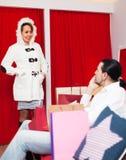 Συνηθισμένο ζεύγος που δοκιμάζει το παλτό στο συναρμολόγηση-δωμάτιο στοκ φωτογραφία