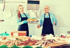 Συνηθισμένο κατάστημα ψαριών και θαλασσινών με τον ευχάριστο χαμογελώντας πωλητή δύο Στοκ Εικόνες