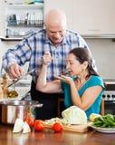 Συνηθισμένο ώριμο ζεύγος που μαγειρεύει από κοινού Στοκ Φωτογραφία