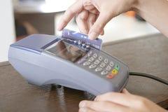Συνοδευτική σκουπίζοντας πιστωτική κάρτα καταστημάτων στο μετρητή καταστημάτων Στοκ Φωτογραφία