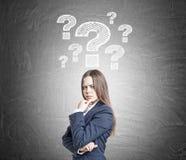 Συνοφρύή γυναίκα και λευκά ερωτηματικά Στοκ φωτογραφία με δικαίωμα ελεύθερης χρήσης