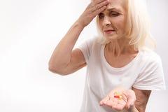 Συνοφρύή ηλικιωμένη γυναίκα που κρατά τα φάρμακα στοκ εικόνες