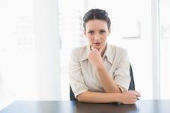 Συνοφρύή μοντέρνη επιχειρηματίας brunette που εξετάζει τη κάμερα και το κράτημα του κεφαλιού της Στοκ φωτογραφία με δικαίωμα ελεύθερης χρήσης