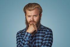 Συνοφρύωμα νεαρός άνδρας που σκέφτεται την έκφραση των αμφιβολιών και των ανησυχιών στοκ φωτογραφία με δικαίωμα ελεύθερης χρήσης