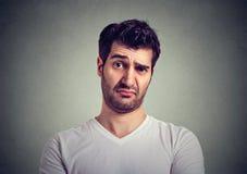 Συνοφρύωμα νεαρός άνδρας που σκέφτεται την έκφραση των αμφιβολιών και των ανησυχιών στοκ εικόνες με δικαίωμα ελεύθερης χρήσης