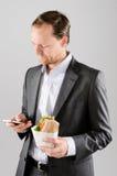 Συνοφρύωμ επιχειρησιακό άτομο με το μεσημεριανό γεύμα και το κινητό τηλέφωνο στοκ φωτογραφία με δικαίωμα ελεύθερης χρήσης