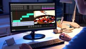 Συντάκτης που εργάζεται στο τηλεοπτικό αρχείο στον υπολογιστή τη νύχτα απόθεμα βίντεο