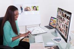 Συντάκτης που χρησιμοποιεί την ψηφιακή ταμπλέτα στην αντιπροσωπεία φωτογραφιών Στοκ εικόνες με δικαίωμα ελεύθερης χρήσης