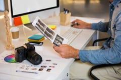 Συντάκτης φωτογραφιών που εργάζεται στο γραφείο υπολογιστών Στοκ εικόνες με δικαίωμα ελεύθερης χρήσης