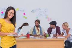 Συντάκτης Prettty που χρησιμοποιεί το lap-top ως εργασίες ομάδων πίσω από την στοκ φωτογραφία με δικαίωμα ελεύθερης χρήσης