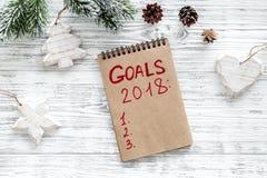 Συντάξτε έναν κατάλογο στόχων για το 2018 Σημειωματάριο και διακόσμηση Χριστουγέννων στην ξύλινη τοπ άποψη υποβάθρου Στοκ Φωτογραφίες