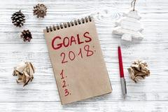 Συντάξτε έναν κατάλογο στόχων για το 2018 Σημειωματάριο και διακόσμηση Χριστουγέννων στην ξύλινη τοπ άποψη υποβάθρου Στοκ Εικόνα