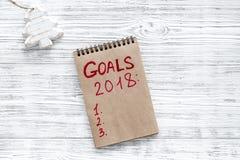 Συντάξτε έναν κατάλογο στόχων για το 2018 Σημειωματάριο και διακόσμηση Χριστουγέννων στην ξύλινη τοπ άποψη υποβάθρου copyspace Στοκ εικόνα με δικαίωμα ελεύθερης χρήσης