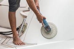 Συντήρηση γιοτ Μια πλευρά στίλβωσης ατόμων της άσπρης βάρκας στοκ εικόνες με δικαίωμα ελεύθερης χρήσης