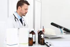 Συνταγή γραψίματος γιατρών στο γραφείο στο ιατρικό γραφείο με τα φάρμακα Στοκ φωτογραφία με δικαίωμα ελεύθερης χρήσης