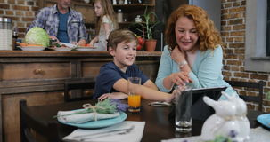 Συνταγή ξεφυλλίσματος οθόνης ταμπλετών αφής μητέρων και γιων ενώ πατέρας με τα τεμαχίζοντας λαχανικά κορών για τη σαλάτα γευμάτων απόθεμα βίντεο