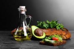 Συνταγή φρυγανιάς αβοκάντο Σάντουιτς δίπλα στο αβοκάντο, τα φύλλα σαλάτας, τη σάλτσα και το ψωμί σε ένα λαμπρό μαύρο υπόβαθρο διά Στοκ Φωτογραφίες