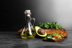 Συνταγή φρυγανιάς αβοκάντο Σάντουιτς δίπλα στο αβοκάντο, τα φύλλα σαλάτας, τη σάλτσα και το ψωμί σε ένα λαμπρό μαύρο υπόβαθρο διά Στοκ Εικόνες