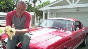 Συνταξιούχος ανώτερη συνεδρίαση ατόμων στην κουκούλα του αποκατεστημένου κλασικού αυτοκινήτου απόθεμα βίντεο