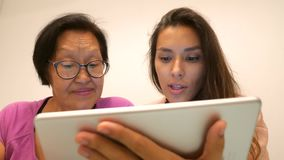 Συνταξιούχος ασιατική γυναίκα με τη νέα μικτή κόρη φυλών που χρησιμοποιεί τη συσκευή ταμπλετών 4K απόθεμα βίντεο