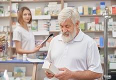 Συνταξιούχος που επιλέγει το φάρμακο στο φαρμακείο στοκ εικόνα με δικαίωμα ελεύθερης χρήσης