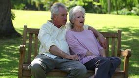 Συνταξιούχος συνεδρίαση ζευγών σε έναν πάγκο απόθεμα βίντεο